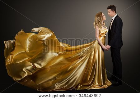 Couple, Beautiful Woman In Golden Silk Dress And Elegant Man In Suit, Gown Fluttering On Wind