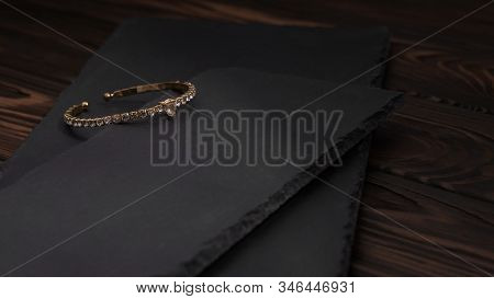 Golden With Diamonds Bracelet On Black Stone Plates. Diamond Golden Bracelet On Rough Textured Stone
