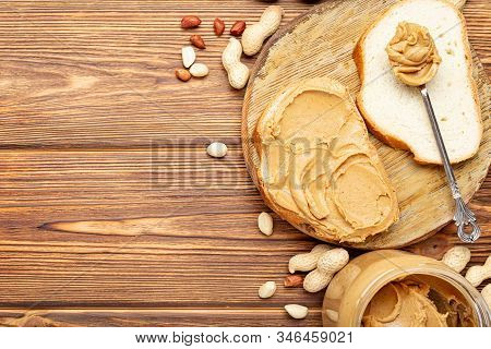 Toast Sandwich With Peanut Butter. Spoon And Jar Of Peanut Butter And Peanuts For Cooking Breakfast