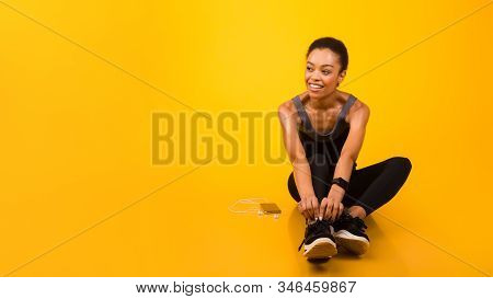 Fitness Lifestyle Concept. Afro Woman In Fitwear Sitting On Floor Ready For Workout Over Yellow Stud