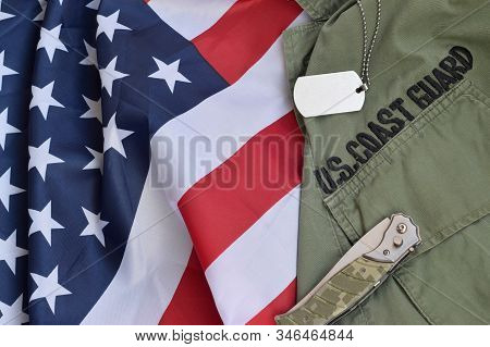 Military Dog Tag Token And Knife Lies On Old Us Coast Guard Uniform And Folded United States Flag