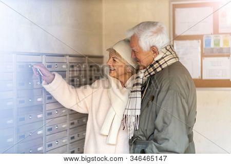 Senior couple unlocking apartment mailbox