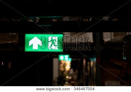 Green Fire Escape Sign Hang On The Ceiling In The Warehouse. The Concept Of Fire Escape Training And