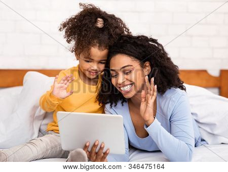 Black Mother And Daughter Using Digital Tablet Making Video Call And Waving Hello Lying In Bed At Ho