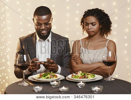 Annoyed Afro Woman Looking At Her Man Using Phone While Having Date In Restaurant, Conflicts In Coup