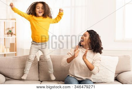 Family Fun. Happy Black Mother And Daughter Having Fun, Kid Jumping On Sofa At Home