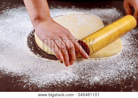 Woman Rolling Dough With Wooden Rolling Pin For Making Buns..