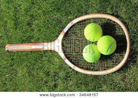 Vintage tennis racket with balls on grass court