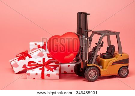 Forklift, red heart and gift boxes on pink background. Valentine's Day. Wedding Day