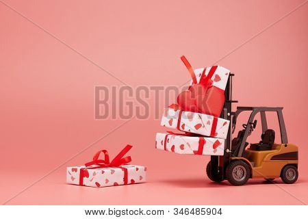 Forklift and gift boxes on pink background with copy space. Valentine's Day. Wedding Day