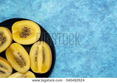 cut gold kiwifruit berries on black plate against blue textured paper with a copy space