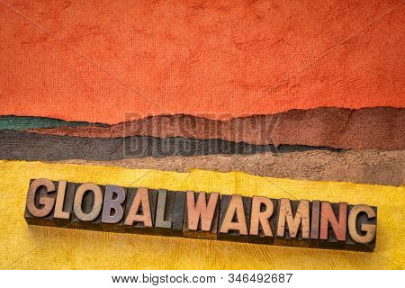 global warming concept - words in vintage letterpress wood type printing blocks against abstract desert landscape, climate change theme