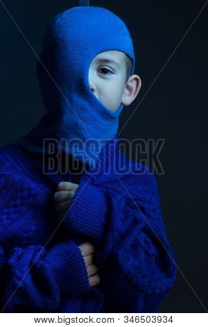 Studio Portrait Of Boy In A Blue Balaclava, Turned On The Left Ear. Tinted In Cold Color
