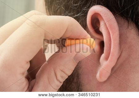Man Putting Ear Plugs Into Ears To Protect Hearing And Get Rid Of Noise. Concept For World Hearing D