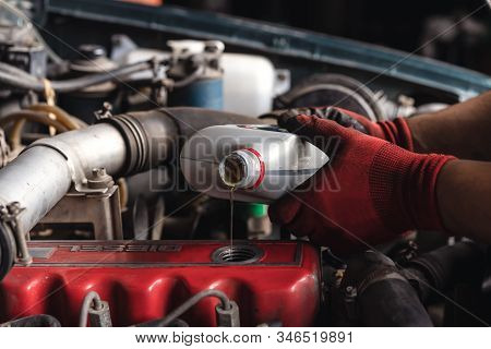 Hands Of Auto Repair Mechanic Filling Lubricant Oil In Engine Of Car During Service - Vehicle Mainte