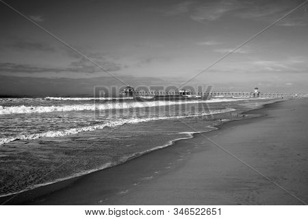 Huntington Beach Pier. Huntington Beach California aka Surf City with the Ocean, Waves, Beach and the World Famous Pier. Black and White.