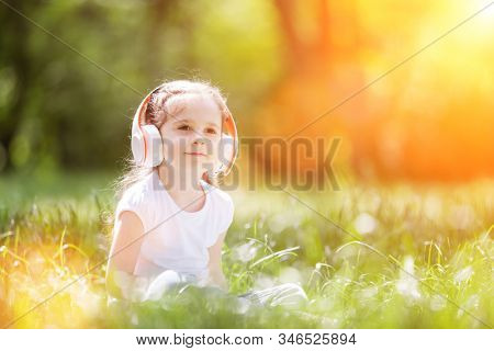 Cute little girl is listening to music in sunny park. Family outdoor lifestyle. Happy small kid in headphones sitting on green grass. Beauty nature at summer. Childhood happiness.  Children day.