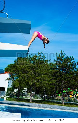 Little Caucasian Female 8 Years Old Girl Diving From Diving Platform.