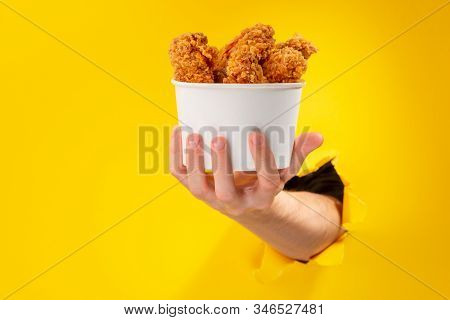 Hand Giving A Whole Cup Of Chicken Nuggets