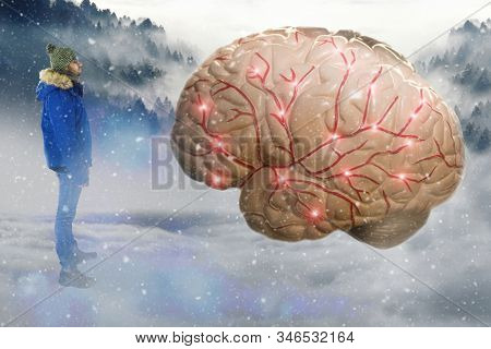 A Man Standing In A Snowy Landscape Staring At A Giant Human Brain. The Brain Is Currently Transmitt