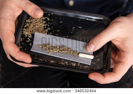 Man Rolling A Marijuana Joint. Drugs Narcotic Concept. Close Up Of Addict Lighting Up Marijuana Join