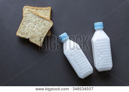 Bottles Of Milk And Pieces Of Bread On Black Background, Healthy Food Concept