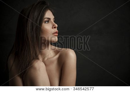 Side View Portrait Of A Beautiful Topless Young Woman Over Black Background.
