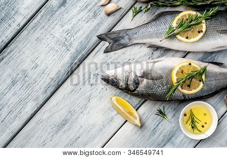 Fresh Fish Sea Bass. Sea Bass Raw Fish With Ingredients Spices And Herbs On Wooden Background