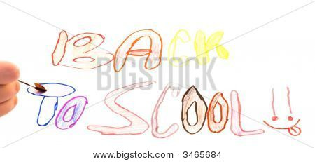A young child's hand holding a paint brush trying to paint in the letters of her artwork poster