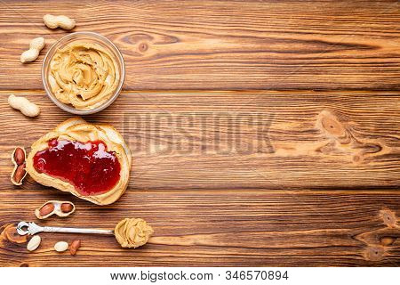 Toast Sandwich With Peanut Butter. Spoon And Jar Of Peanut Butter, Jam And Peanuts For Cooking Break