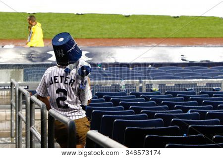 BRONX, NY - JUL 18: A fan waits for the rain to stop during the seventh inning rain delay at the game between the New York Yankees and the Toronto Blue Jays on July 19, 2012 at Yankee Stadium.