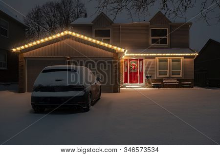 Nighttime Shot Of A Detached Suburban House With A Red Door All Lit Up With Christmas Lights