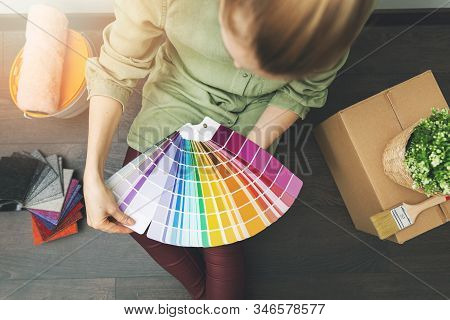 Woman Sitting On The Floor In The Room And Choosing Paint Color From Swatch For New Interior Design