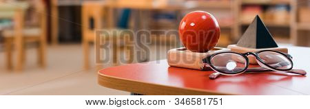 Panoramic Shot Of Educational Game And Eyeglasses On Desk In Montessori School