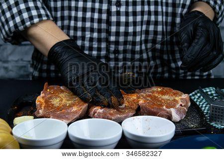 A Chef In Black Gloves Rubs Into The Meat A Raw Tenderloin. Fresh Raw Pork Tenderloin On A Wooden Cu
