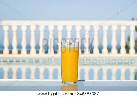 Freshly Squeezed Orange Juice In The Summer With Views On Swimming Pool And The Sea, Glass Of Orange