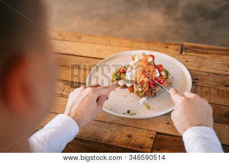 Young Man Enjoys Big And Tasty Breakfast At Cafe. Delicious Sandwich Or Toast With Avocado And Smoke