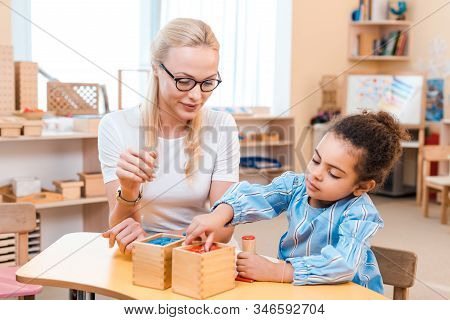 Teacher And Kid Folding Wooden Game At Desk In Montessori School