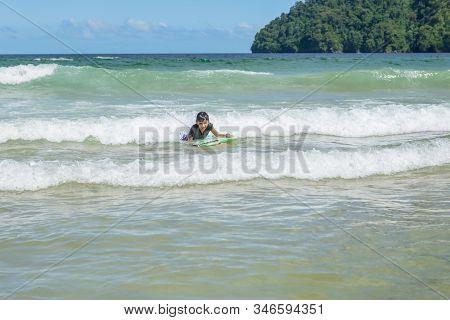 Older Boy Swimming In Maracas Bay Beach Trinidad And Tobago Having Fun Riding Waves Looking