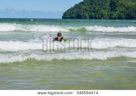 Older Boy Swimming In Maracas Bay Beach Trinidad And Tobago Having Fun Riding Waves