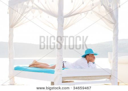 Woman in hat relaxing on luxury white bed at the sea poster