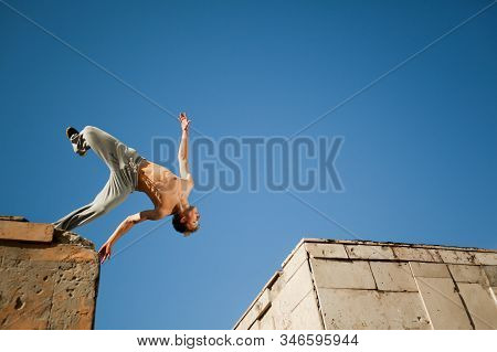 Young Man Jumping And Practicing Parkour Between Two Buildings Outside On Clear Summer Day With Blue