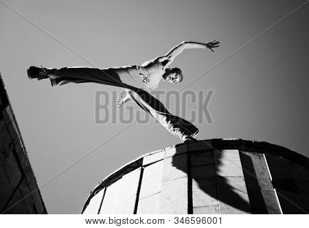 Young Man Jumping And Practicing Parkour Between Buildings Roofs Outside On Clear Summer Day With Bl