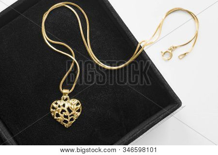 Gold Necklace With Carved Heart Shaped Pendant In Black Jewel Box Closeup