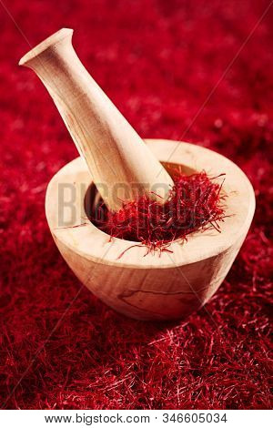 saffron threads in mortar with pestle, truly color, huge amount of spice , soft focus