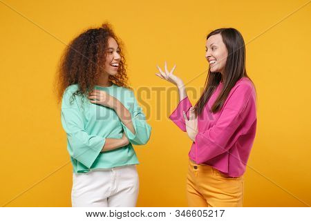 Two Cheerful Women Friends European And African American Girls In Pink Green Clothes Posing Isolated