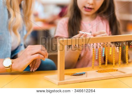 Selective Focus Of Kid Playing Wooden Game By Teacher In Montessori School, Cropped View