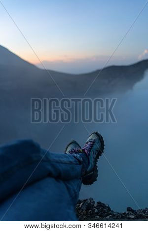 Adventure Seeker Sitting On The Cliff And Enjoying The View Of Acid Lake In Ijen Volcano Crater At S