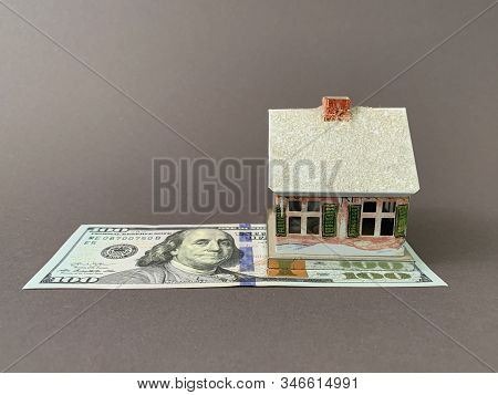 House With A Foundation On A Hundred Dollar Bill. A Toy House With A Roof Costs Money. Concept: Mort