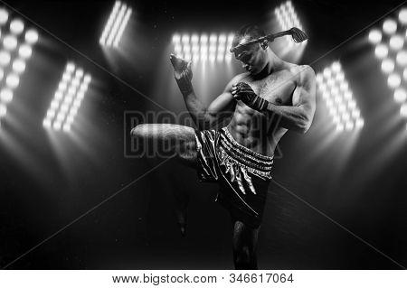 Kickboxer In The Ring Surrounded By Searchlights Stretches Before The Fight. Makes Swing Movements W